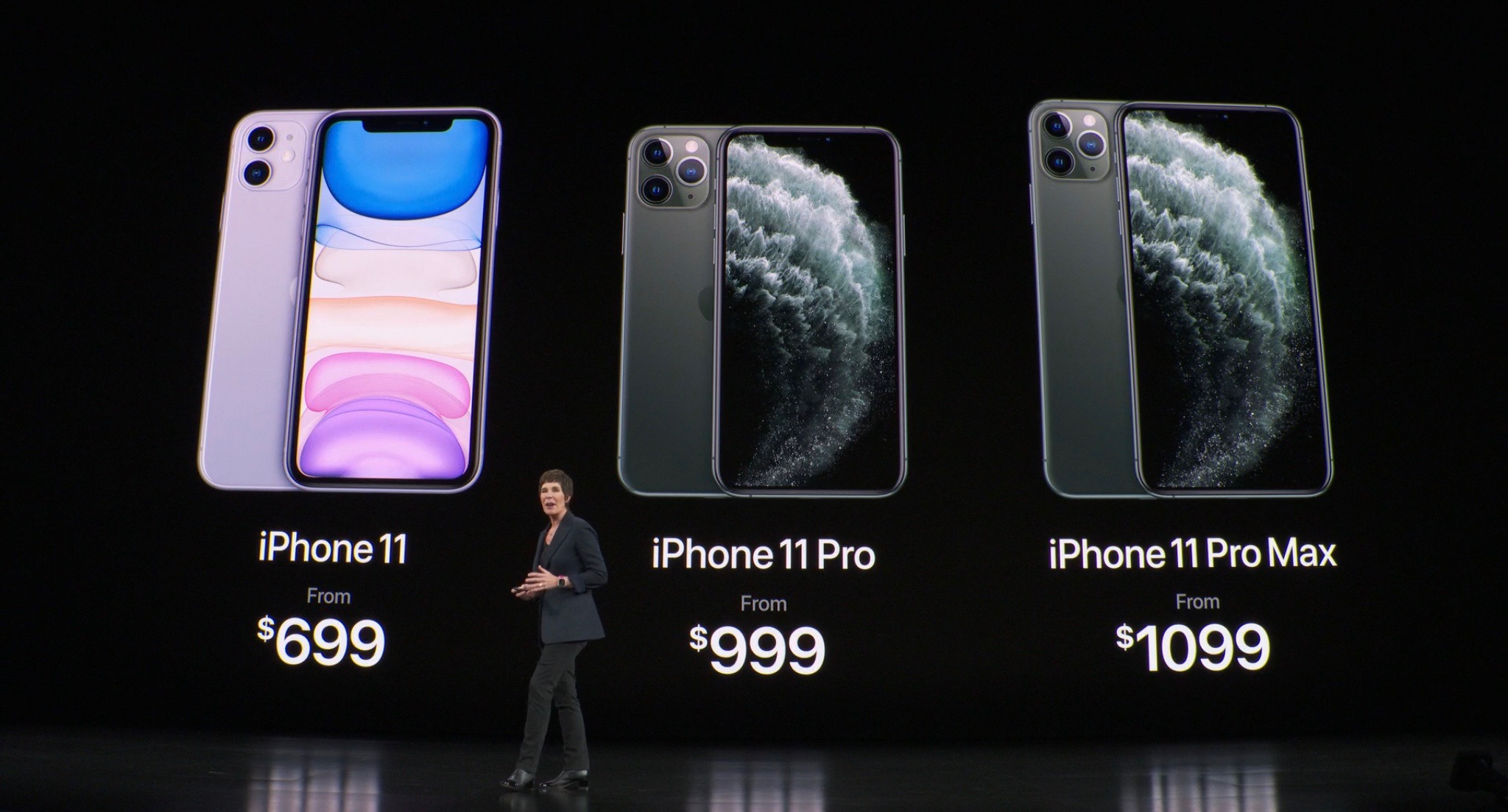 Apple exec in front of massive screen showing three models of iPhone 11, including prices.
