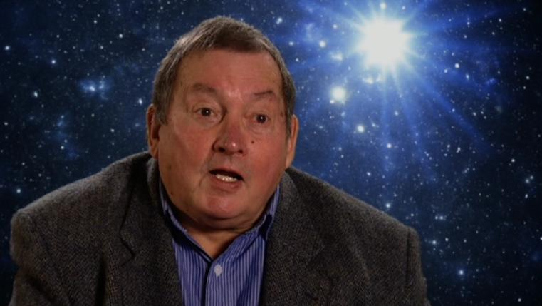 "Screengrab of Terrance Dicks taken from a BBC DVD ""Extra"", talking against a background of stars."
